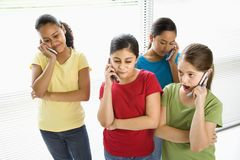 Preteen girls. Preteen girls of mutiple ethnicities talking on cell phones Royalty Free Stock Photography
