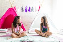 Girls Sitting Against Teepee Tents During Slumber Party. Preteen girls looking at each other while sitting against teepee tents during slumber party royalty free stock photos