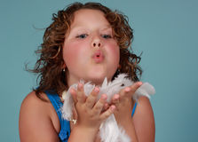 Preteen gril and white feathers. Preteen girl blowing on white feathers Royalty Free Stock Image