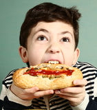 Preteen handsome boy bite big hotdog Royalty Free Stock Images