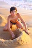Preteen handsome boy build sand caslte Stock Photo