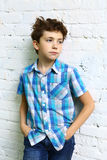 Preteen handsome boy in checked blue shirt. Close up portrait on white brick wall background stock photos