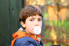 Preteen handsome boy with chewing gum bubble close up counrty po Royalty Free Stock Photos