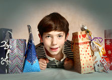 Preteen handsome boy with christmas presents Stock Photos