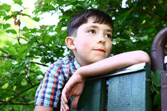 Preteen handsome boy climb village fence. Close up portrait on the summer green backgroun royalty free stock photos