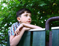 Preteen handsome boy climb village fence. Close up portrait on the summer green backgroun royalty free stock photography