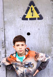Preteen handsome boy on front of the door with electricity warni Stock Photos