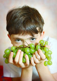 Preteen handsome boy with green grapes close up portrait Stock Image