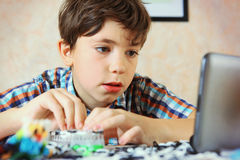 Preteen handsome boy have an online lesson how to make rainboy l royalty free stock photos