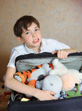 Preteen handsome boy pack  his coffer with toys before trip Stock Photo