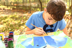 Preteen handsome boy painting with gouache Stock Photo