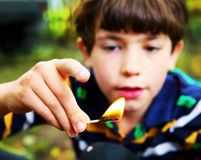 Preteen handsome boy play with fire hold match royalty free stock photos