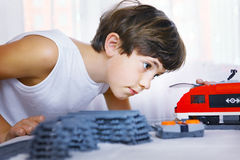 Preteen handsome boy play with meccano toy train and railway sta Royalty Free Stock Photos