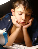 Preteen handsome boy read book with lamp before sleep Royalty Free Stock Images