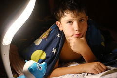 Preteen handsome boy read book with lamp before sleep royalty free stock photos