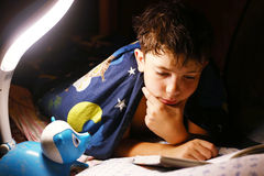 Preteen handsome boy read book with lamp before sleep Royalty Free Stock Photography