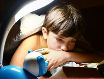Preteen handsome boy read book with lamp Stock Photo