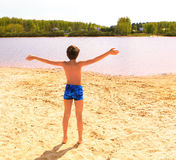 Preteen handsome boy on the shore of the country lake Stock Image