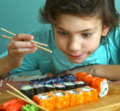 Preteen handsome boy with sushi roll set Royalty Free Stock Photo