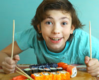 Preteen handsome boy with sushi roll set Stock Images