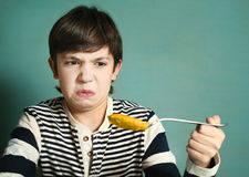 Preteen handsome boy with tablespoon of pumpkin soup Stock Images