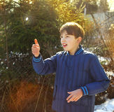 Preteen handsome boy toss a coin. On the country spring sunny village background Royalty Free Stock Photo