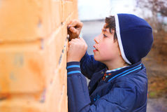 Preteen handsome boy try himself as a graffiti artist on the yel. Preteen handsome boy try himself as a graffiti artist  on the yellow brick wall Stock Images
