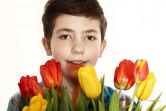 Preteen handsome boy with tulip flowers Royalty Free Stock Photo