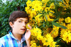 Preteen handsome boy with yellow big flowers close up portrait Stock Images