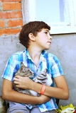 Preteen handsome country boy with kitten close up portrait Stock Images