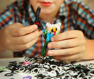 Preteen hansome boy show  the  result of his rainbow loom  hobby Stock Photo