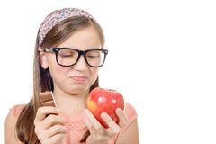 Preteen hesitates between chocolate and an apple Stock Photography