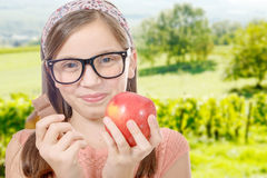 Preteen hesitates between chocolate and an apple Royalty Free Stock Photo