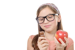 Preteen hesitates between chocolate and an apple Stock Images