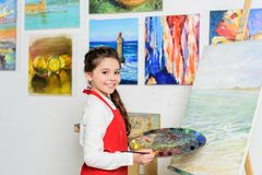Preteen kid holding palette near canvas in workshop of. Art school royalty free stock images