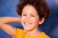 Preteen krullende jongen die en camera lachen bekijken stock foto