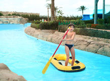 Preteen little boy in aqua park swim in rubber boat with row. Preteen little boy in aqua  park swim in rubber boat with row Royalty Free Stock Photography