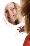 Preteen Looking In Mirror. A smiling preteen girl is looking at herself in a small mirror, isolated against a white background Stock Photos
