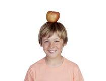 Preteen met een rode appel op zijn hoofd stock fotografie