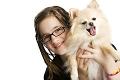 Preteen and Pet. Happy preteen with lots of braids holding her pet Pomeranianl.  Isolated on white Royalty Free Stock Photography