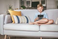 Preteen pojke losted i dataspel Sitter hemma p? cozesoffan, bruksgamepad med smartphonen arkivfoton