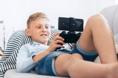 Preteen pojkebruksgamepad med smartphonelekar spelar att ligga p? den hemtrevliga soffan i den hem- vardagsrummet royaltyfria bilder