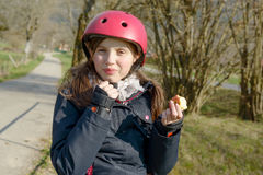 Preteen with roller skate helmet, eat an apple Royalty Free Stock Images
