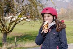 Preteen with roller skate helmet, eat banana Stock Image