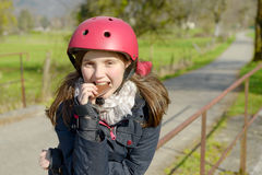 Preteen with roller skate helmet, eat a cake Stock Images
