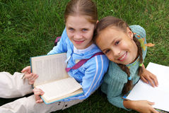 Preteen school girls reading books. On green grass background outdoors Royalty Free Stock Images