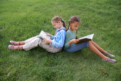 Preteen school girls reading books. On green grass background outdoors Royalty Free Stock Image