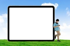 Preteen schoolboy leaning on a blank whiteboard. Picture of a preteen schoolboy looking his smartphone while leaning on a blank whiteboard. Shot in the meadow royalty free stock photography