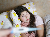 Preteen sick girl in bed with thermometer Royalty Free Stock Photo