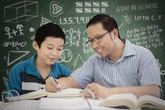 Preteen studencki uczenie czytać z jego nauczycielem Zdjęcia Stock